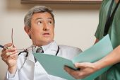 Mature male doctor staring while technician holding patient's file