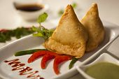 stock photo of samosa  - Samosa is an Indain fried or baked pastry with a savory filling with spiced potatoes onions peas lentilsChana - JPG