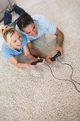 High angle view of a couple playing video games on area rug at home