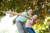 Low angle portrait of a happy mother and daughter with arms outstretched at the park