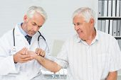Male doctor taking a senior patients pulse at the medical office