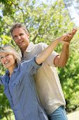Tilt image of romantic couple with arms outstretched in park