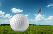 Golf ball on green grass close up and the flag