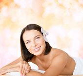 health and beauty, resort and relaxation concept - beautiful woman with flower in her hair in spa sa
