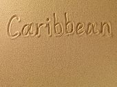The word Caribbean is written on a sand background