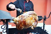 stock photo of spit-roast  - Carcass roasted lamb on a spit and cook - JPG