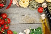 Fresh ingredients for cooking: pasta, tomato and spices over wooden table background with copy space