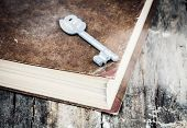 stock photo of skeleton key  - closed old book on grunge wood desk with key - JPG