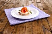 Pancake with salmon and mayo, green onion, on plate, on color napkin, on wooden background