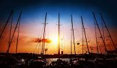 Sailboats mast on beautiful sunset background, harbor for sail yacht in the night, old marina in European city, travel and tourism concept