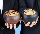 Two ceramic pots with golden coins in male and female hands, on color background