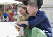 Mature Couple Working On Laptop Outdoors
