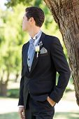Bridegroom looking away while standing in garden