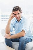 Man with headache sitting on the couch looking at camera at home in the living room