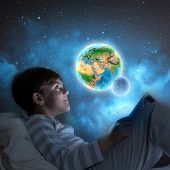 Little cute boy sitting in bed and using tablet. Elements of this image are furnished by NASA