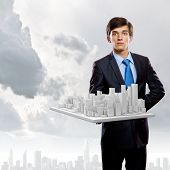 Handsome businessman holding model of modern city