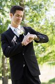 Young smart bridegroom checking time in garden