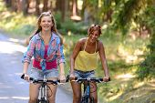 Two teenage girls riding their bikes laughing enjoy summer sport