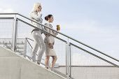 Profile shot of businesswomen moving down stairs against sky