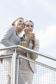 Young businesswoman with disposable coffee cup pointing while standing with coworker by railing agai