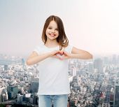 advertising, childhood, charity and people concept - smiling little girl in white t-shirt making heart-shape gesture over city background