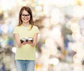 people and vision concept - smiling cute little girl in black eyeglasses holding many glasses in her