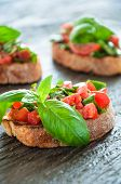 Italian Bruschetta With Chopped Vegetables, Herbs And Oil On Grilled Or Toasted Crusty Ciabatta Brea