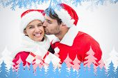 Attractive festive man giving girlfriend a kiss and present against frost and fir trees