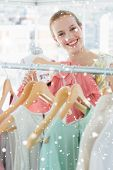 Happy female customer selecting clothes in store against snow falling