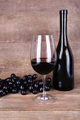 Tasty wine and ripe grape on wooden background
