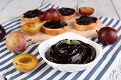 Bowl of plum jam, slices of bread with plum jam and fresh plums on cutting board on napkin on wooden background