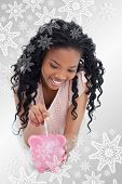 A young girl lying on the floor putting money into a piggy bank against snowflakes on silver