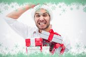 Stressed festive man holding gifts against snow flake frame in green