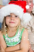 Girl wearing Santa hat at home against snow falling