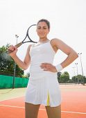 Pretty tennis player holding racket smiling at camera on a sunny day