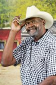 A mature African American cowboy ready to tip his hat in greeting.