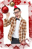 Geeky hipster in party hat pointing against christmas themed page