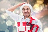 Festive man holding christmas gifts against light glowing dots design pattern