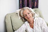 Senior woman sleeping on armchair at home