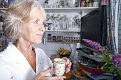 Thoughtful senior woman looking away while holding coffee cup in kitchen