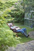 Full length of senior man sleeping on deckchair in backyard