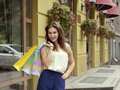 Young woman with shopping bags near shop