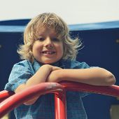Cute young boy playing on playground.