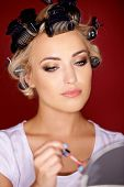 Beautiful young woman with her blond hair in curlers as she holds lipstick while looking in a mirror