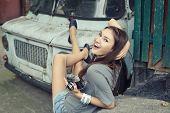 Urban girl has fun with vintage photo cameras outdoor near retro car, image toned.