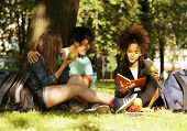 cute group of teenages at the building of university with books huggings, diversity nations