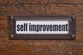 self improvement  - file cabinet label, bronze holder against grunge and scratched wood