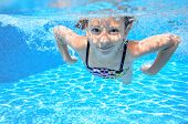 foto of swimming pool family  - Happy active underwater child swims in pool - JPG
