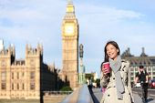 London woman happy by Big Ben laughing and drinking coffee in autumn. Young female professional on Westminster Bridge, London, England. Beautiful young multiracial Asian Caucasian girl.