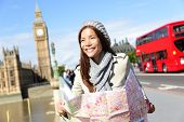 Travel London tourist woman on Europe sightseeing holding map by Big Ben and red double decker bus. Tourism people concept with mixed race Asian girl smiling happy, Westminster Bridge, London, England